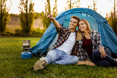 Camping time. Shot of a happy couple camping on the nature and pointing to somewhere Stock Image