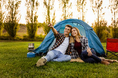 Camping time. Shot of a happy couple camping on the nature and pointing to somewhere Royalty Free Stock Photography