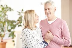 Cheerful senior couple having fun together. Shot of a happy senior couple standing at home and embraching eachother while looking at camera and smiling Royalty Free Stock Photography