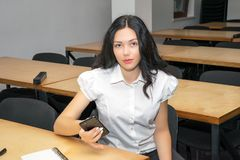 Cute girl sitting at desk in classroom using smartphone. Education concept photo stock photo