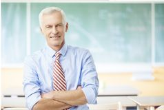 Male teacher in the school. Shot of a hapyy male teacher standing in the lecture hall in front of the chalkboard Stock Photos
