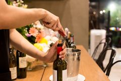 Shot in high iso with low light man opening bottle of wine with. Corkscrew at party stock photo