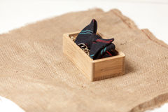 Shot of hipster bow tie in wooden box lying on burlap Stock Image