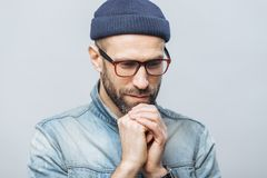 Shot of hopeful bearded male looks with thoughtful expression down, keeps hands together, hopes for better, worships in calm atmos stock image