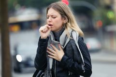 Illness young woman coughing in the street royalty free stock photography