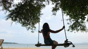 Woman swinging at tropical beach, sunny day, good weather. Swinging in paradise island. Shot in 4k, suitable for commercial use stock video footage