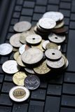 A shot of a laptop and world coins Stock Photo