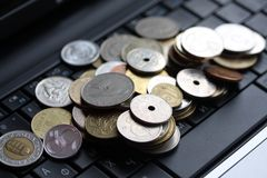 A shot of a laptop and world coins Stock Photography