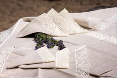 Shot of linen tablecloth and napkins with lace trim. Shot of linen tablecloth and napkins with grey lace trim, barley and flowers stock images
