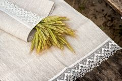 Shot of linen towels, tablecloths, napkins with lace trim. Shot of linen tablecloths, towels and napkins with grey and white lace trim, pine cone, flowers and royalty free stock photos