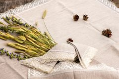 Shot of linen towels, tablecloths, napkins with lace trim. Shot of linen tablecloths, towels and napkins with crochet white lace trim, pine cone, flowers and royalty free stock photos