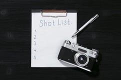 Shot list. Shot list mockup. Vintage film photo camera paper page on black wooden table background royalty free stock images