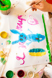Shot of little girl drawing blue rabbit on canvas Royalty Free Stock Photo