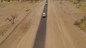A shot of a long road with cars passing by. A birds eye view shot of a long road with grass and trees on land with cars passing by in slow motion. Camera slowly stock video
