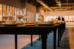Shot of the long table that is set with dishes and many have fallen and broken Stock Photo
