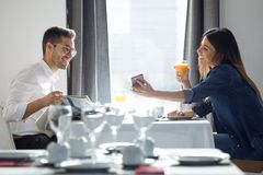 Lovely attractive couple enjoying breakfast and looking photos in smartphone in the dining room of the hotel stock images