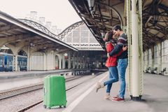 Shot of lovely boyfriend and girlfriend stand closely, embrace and kiss, wait for transport on railway station, being passengers, stock photos