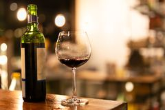 Shot in low light and high iso bottle and glass of red wine on wooden top. Shot in low light and high iso bottle and glass of red wine on wooden top stock photography