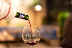 Shot in low light and high iso red wine pouring down from wine bottle. royalty free stock images