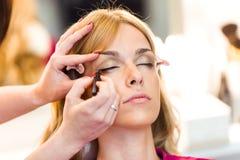 Make-up artist doing make-up beautiful woman in the beauty salon. Shot of make-up artist doing make-up beautiful woman in the beauty salon stock images