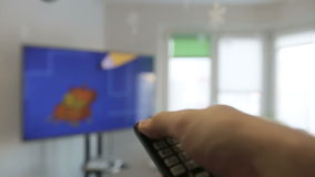 Shot of a male hand holding the TV remote control and turn off the television. stock video footage