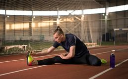 Male track and field athlete stretching and relaxing after the training. The shot of male track and field athlete stretching and relaxing after the training Royalty Free Stock Image