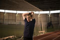 Male track and field athlete warming up before the training.Indoor training. The shot of male track and field athlete warming up before the training.Indoor stock photography