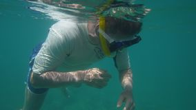 Exploring the deep sea near an inflatable boat. A shot of a man exploring the deep sea. The man is near an inflatable boat stock footage