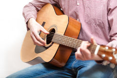 Shot of man in shirt and jeans playing on classic guitar Stock Images