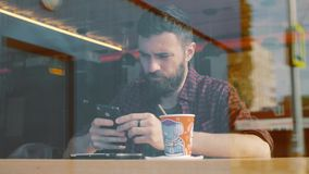 Shot of a man sitting in cafe with a smartphone. Shot through cafe show window. stock video footage