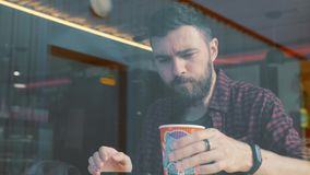 Shot of a man sitting in cafe with a smartphone. Shot through cafe show window. stock footage