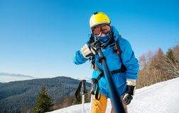 Male skier using selfie stick taking photos while skiing. Shot of a man skier wearing ski equipment taking a selfie using monopod at the winter resort. Blue sky Royalty Free Stock Photos