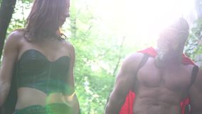 Medieval warrior in working out in the woods with his woman. Shot of a mature warrior woman and her man both wearing battledresses working out together in the stock video