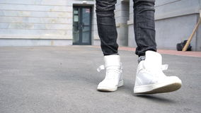 Shot of men legs in sneakers walking on tile road. stock footage