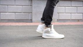 Shot of men legs in sneakers walking on tile road. stock video footage