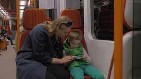 Shot of mother and son ride in the subway train and go out on the station, Prague, Czech Republic. Shot of woman with son riding in the subway, son playing on stock footage