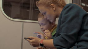 Shot of mother and son ride in the subway train using smartphone during trip, Prague, Czech Republic. Shot of woman with son riding in the subway train using stock video