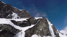 Chair lift rises up to the top of the mountain with rocks in winter ski resort. Shot in motion with a ski chairlift that rises to the top of the beautiful snow stock video footage