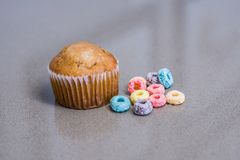 It`s a Breakfast Time Muffin and Cereal. A shot of a muffin and some fruit loops on a table Stock Photos