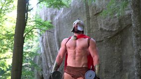 Medieval warrior in working out in the woods. Shot of a muscular medieval soldier in a battledress showing off his perfect strong sexy body working out outdoors stock video footage