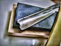 Straight Razor. A shot of my straight razor, open blade, sitting on a wooden box, edited Stock Photos