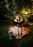 Shot at night of woman reading book at light of garden lantern Royalty Free Stock Images