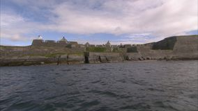 An old castle from a far. A shot from the ocean of an old castle in Ireland. The shot is in extreme long shot stock video footage