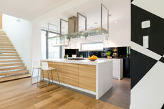Kitchen island is the part of every modern interior. Shot of an open kitchen room interior with a kitchen island and a hood over countertop Stock Photos