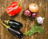 Shot, organic vegetables, healthy food concept. Eggplant with garlic onion paprika allspice fennel lie on the board top view Royalty Free Stock Photo