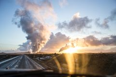 Smoke out of geothermal pipes against dramatic sunset sky. Shot out of a car, urbanization and global warming, roadtrip in Iceland Royalty Free Stock Photos