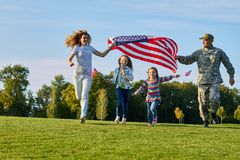 Shot of patriotic family running with flag. US soldier and his happy family stock image