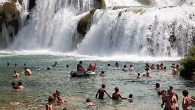 Shot of the people swimming under the waterfall in Krka national park