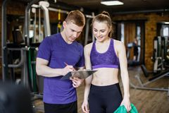 Shot of a personal trainer helping a gym member with her exercise plan. Trainer goes through fitness plan with client in the health club Stock Images