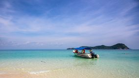 Boat in secluded white sandy beach royalty free stock photography